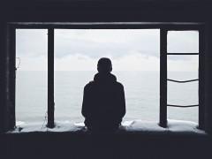 Silhouette einer Person vor einem Fenster