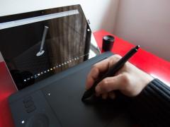 Hand mit Stylus auf einem Wacom-Grafiktablett und Anzeige auf dem Surface-Tablet