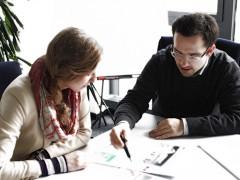 Usability-Experte bespricht Wireframes einer Website mit Kundin (© itemis AG)